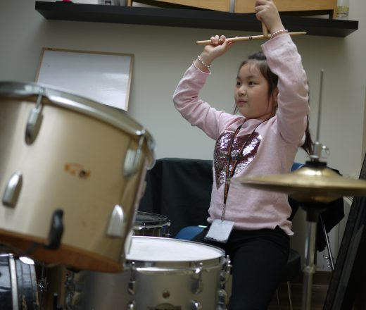 Girl plays drums at Girls Rock Camp