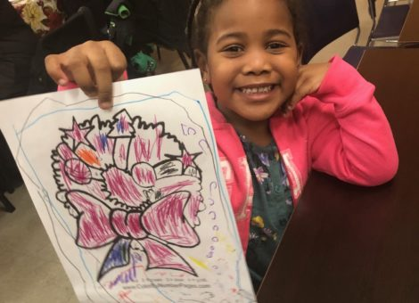 photo of girl at christmas party holding colouring book