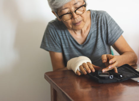 Senior woman with glucometer checking blood sugar level at home