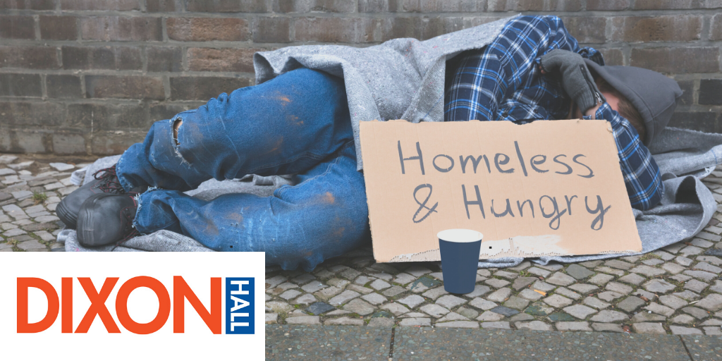 Man lying on street with Homeless & Hungry sign