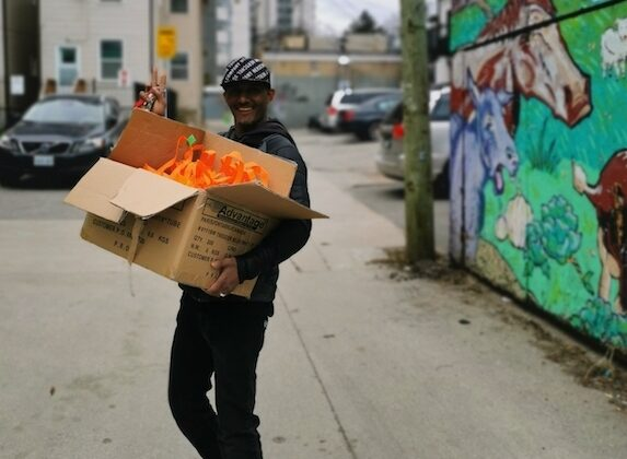 Volunteer carrying a box full of supplies